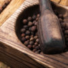 Black fragrant pepper peas in a stylish wooden mortar
